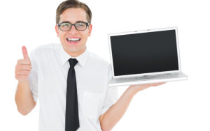 smiling man while holding a laptop